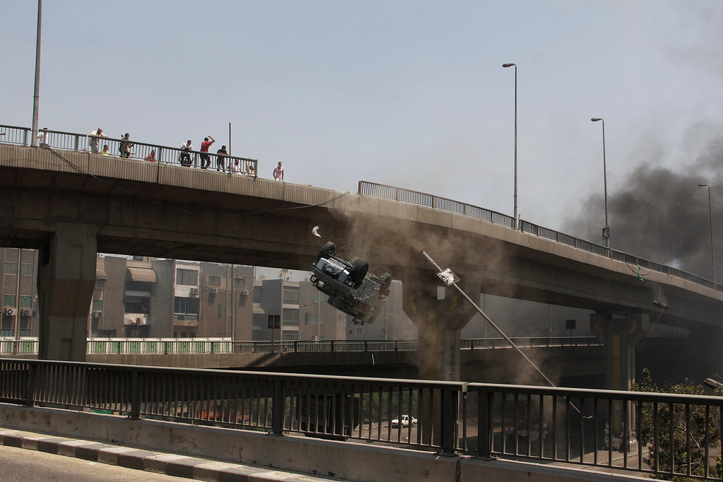 . A police vehicle is pushed off of the 6th of October bridge by protesters close to the largest sit-in by supporters of ousted Islamist President Mohammed Morsi in the eastern Nasr City district of Cairo, Egypt, Wednesday, Aug. 14, 2013.  (AP Photo/Aly Hazzaa, El Shorouk Newspaper)