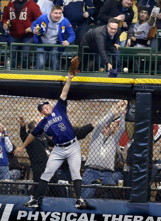 . Colorado Rockies\' Michael Cuddyer leaps but can\'t catch Milwaukee Brewers\' Norichika Aoki\'s home run in the third inning of an Opening Day baseball game  Monday, April 1, 2013, in Milwaukee. (AP Photo/Jeffrey Phelps)