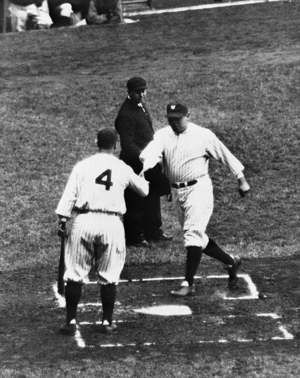 . Babe Ruth crosses the plate with a run, date unknown. Welcoming him to the plate is Lou Gehrig (4). (AP Photo)