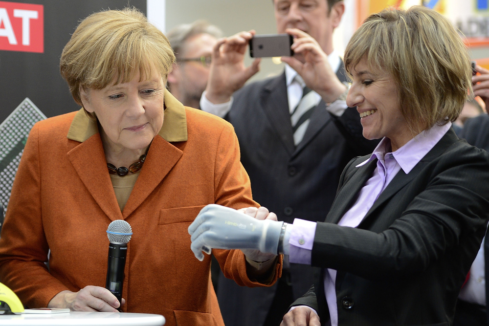Description of . Claudia Breidbach (R) shows German Chancellor Angela Merkel how to control her bionic hand I-Limb on the stand of Great Britain's Touch Bionic company the 2014 CeBIT technology Trade fair on March 10, 2014 in Hanover, Germany. CeBIT is the world's largest technology fair and this year's partner nation is Great Britain.  (Photo by Nigel Treblin/Getty Images)