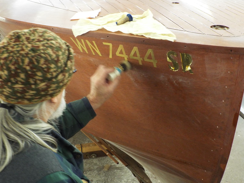 Gold leaf being applied to the registration numbers.