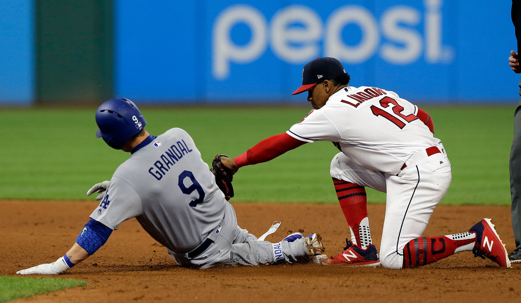 . Cleveland Indians\' Francisco Lindor tags out Los Angeles Dodgers\' Yasmani Grandal after Grandal tried to stretch a single into a double during the eighth inning of a baseball game, Tuesday, June 13, 2017, in Cleveland. (AP Photo/Tony Dejak)