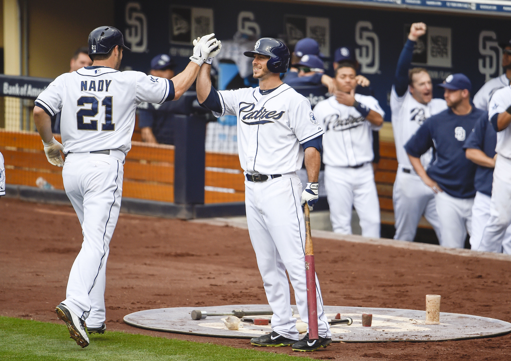 . Xavier Nady #21 of the San Diego Padres, left, is congratulated by Tommy Medica #14, center, after hitting a solo home run during the fourth inning of a  baseball game against the Colorado Rockies at Petco Park April 17, 2014 in San Diego, California.  (Photo by Denis Poroy/Getty Images)