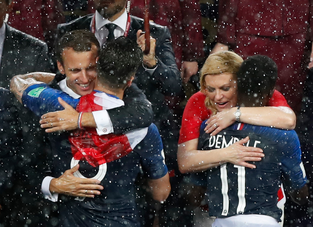 . French President Emmanuel Macron, left, and Croatian President Kolinda Grabar-Kitarovic congratulate French players on their victory as they are presented with medals after the final match between France and Croatia at the 2018 soccer World Cup in the Luzhniki Stadium in Moscow, Russia, Sunday, July 15, 2018. France won the final 4-2. (AP Photo/Rebecca Blackwell)