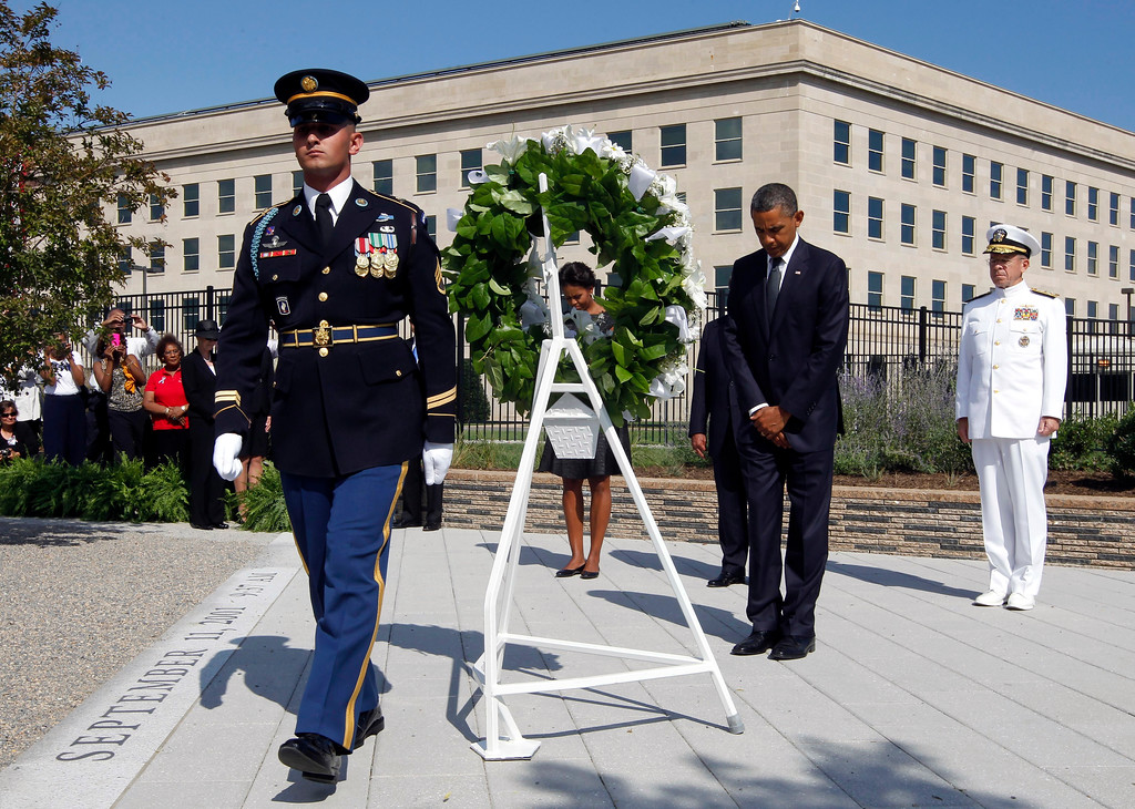 . President Barack Obama and first lady Michelle Obama bow during a wreath laying to mark the 10th anniversary of the Sept. 11 attacks at the Pentagon in Washington, Sunday, Sept. 11, 2011. At right is Chairman of the Joint Chiefs of Staff Adm. Michael Mullen. (AP Photo/Charles Dharapak)