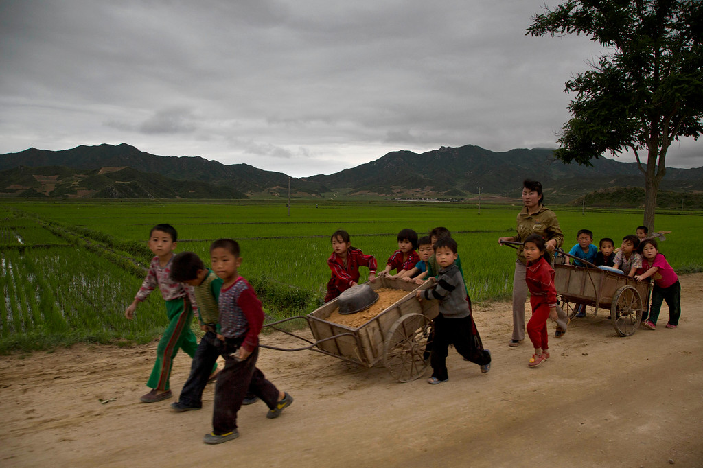 """. In this June 20, 2014 photo, young North Korean schoolchildren help to fix pot holes in a rural road in North Korea\'s North Hamgyong province. The Associated Press was granted permission to embark on a weeklong road trip across North Korea to the countryís spiritual summit Mount Paektu. The trip was on North Korea\'s terms.  An AP reporter and photographer couldn\'t interview ordinary people or wander off course, and government \""""minders\"""" accompanied them the entire way. (AP Photo/David Guttenfelder)"""