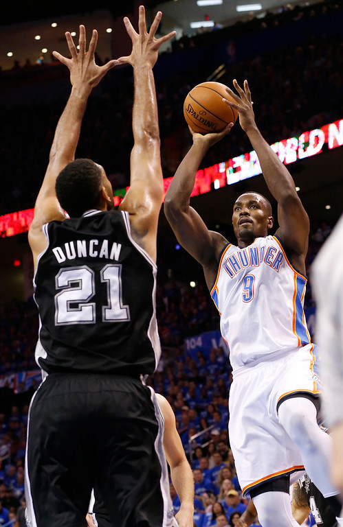 . Oklahoma City Thunder forward Serge Ibaka (9) shoots in front of San Antonio Spurs forward Tim Duncan (21) in the first quarter of Game 3 of an NBA basketball playoff series of the Western Conference finals, Sunday, May 25, 2014, in Oklahoma City. (AP Photo/Sue Ogrocki)