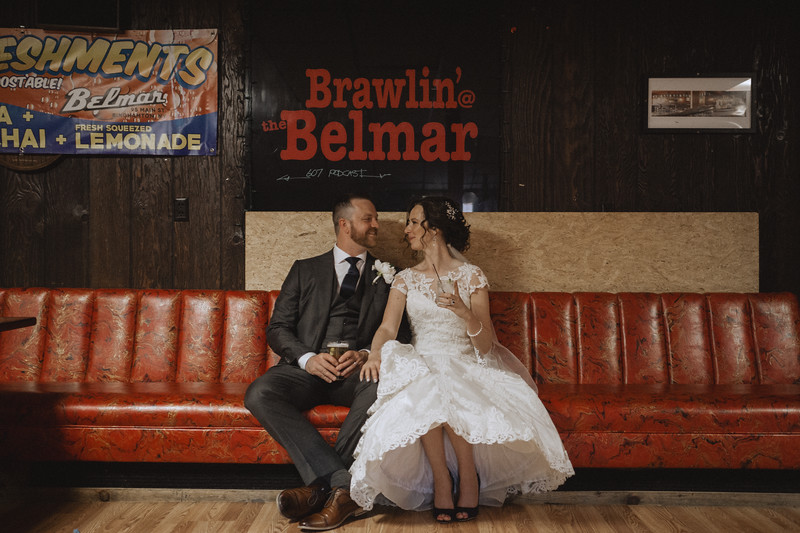 The bride and groom sit on a long booth with drinks in their hands as they smile at each other.