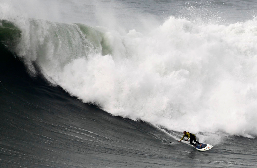 . US surfer Garrett McNanamara rides a wave during a surf session at Praia do Norte beach in Nazare, Portugal, Wednesday, Jan. 30, 2013. McNamara is said to have broken his own world record for the largest wave surfed when he caught a wave reported to be around 100ft,  off the coast of Nazare on Monday.  If the claims are verified, it will mean that McNamara, who was born in Pittsfield, Massachusetts, USA,  but whose family moved to Hawaii\'s North Shore when he was aged 11, has beaten his previous record, which was also set at Nazare, of 23.77 meters (78 feet) in November 2011. (AP Photo/Francisco Seco)