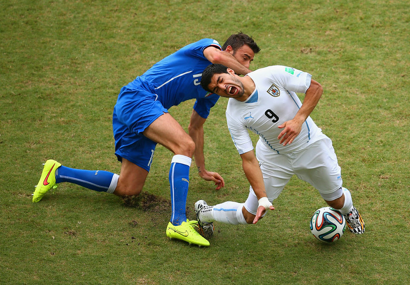 . Andrea Barzagli of Italy challenges Luis Suarez of Uruguay during the 2014 FIFA World Cup Brazil Group D match between Italy and Uruguay at Estadio das Dunas on June 24, 2014 in Natal, Brazil.  (Photo by Julian Finney/Getty Images)