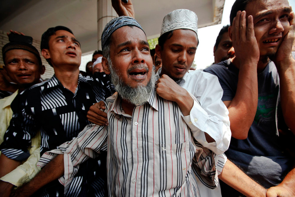 . People react as the bodies of victims of a fire are brought for their funeral at Yaeway cemetery in Yangon on April 2, 2013. Thousands of Muslims attended the funeral for the 13 victims of the fire that broke out in a dormitory of an Islamic school in the central, multi-ethnic Botataung district of the former capital. The fire caused by faulty electrical equipment killed 13 boys at the school in Yangon on Tuesday, the fire service said.     REUTERS/Minzayar