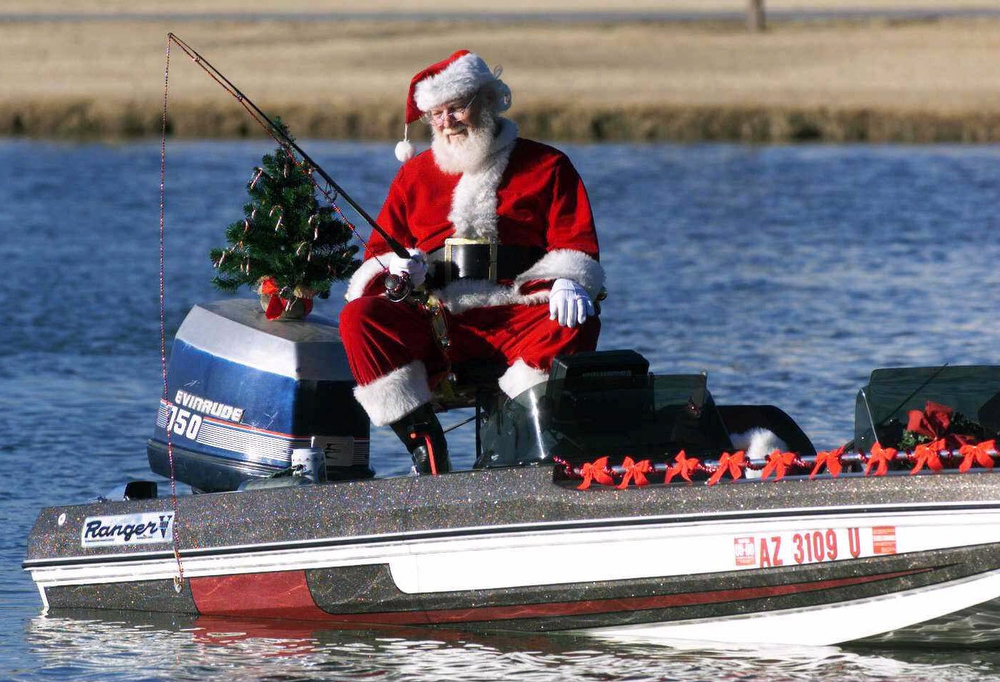 Description of . 'Santa Claus'  Bob Greathouse, takes a day off from his busy holiday schedule for a morning of fishing at Chaparral Lake in Scottsdale, Ariz., on Wednesday, Dec. 22, 1999. Santa's bait of choice? A candy cane, of course. (AP photo/the Tribune, Irwin R. Daugherty)