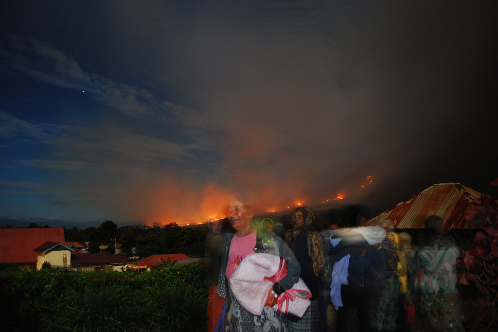 . Residents flee from latest Mount Sinabung volcano eruption as scorching lava rolls down from the crater threatening villages on October 8, 2014, seen from Karo district located on Indonesia\'s Sumatra island, following an earlier eruption on October 5, 2014. AFP PHOTO / SUTANTA  ADITYA/AFP/Getty Images