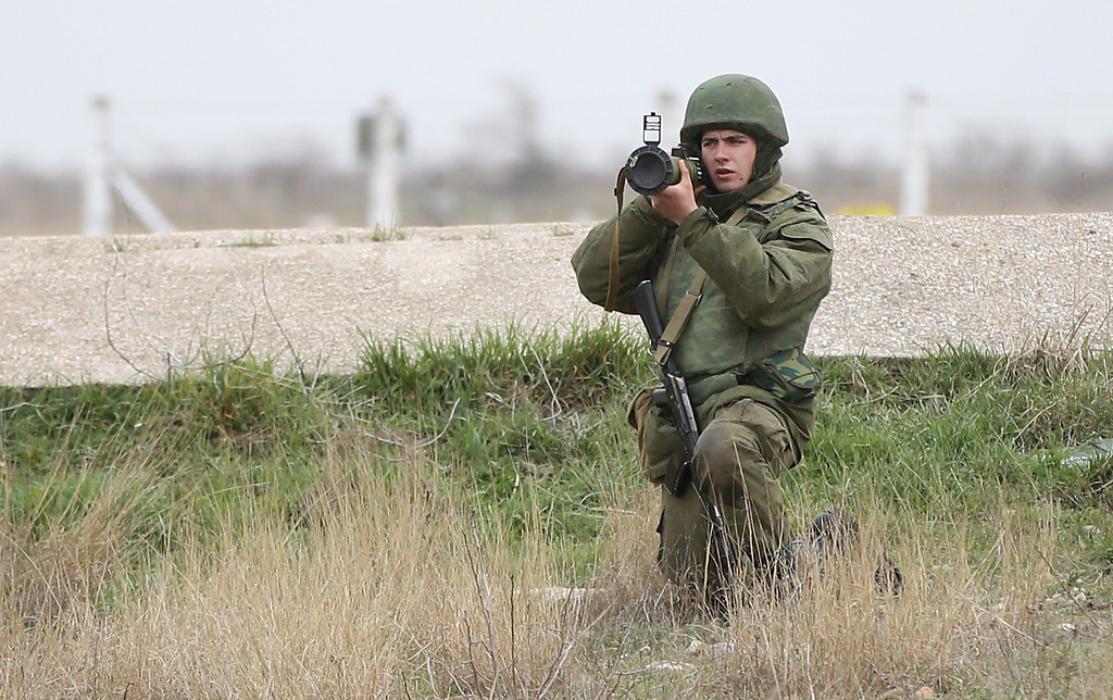 . A soldier under Russian command aims a rocket propelled grenade launcher at a group of over 100 hundred unarmed Ukrainian troops who appeared at the Belbek airbase, which the Russian troops are occupying, in Crimea on March 4, 2014 in Lubimovka, Ukraine.  (Photo by Sean Gallup/Getty Images)