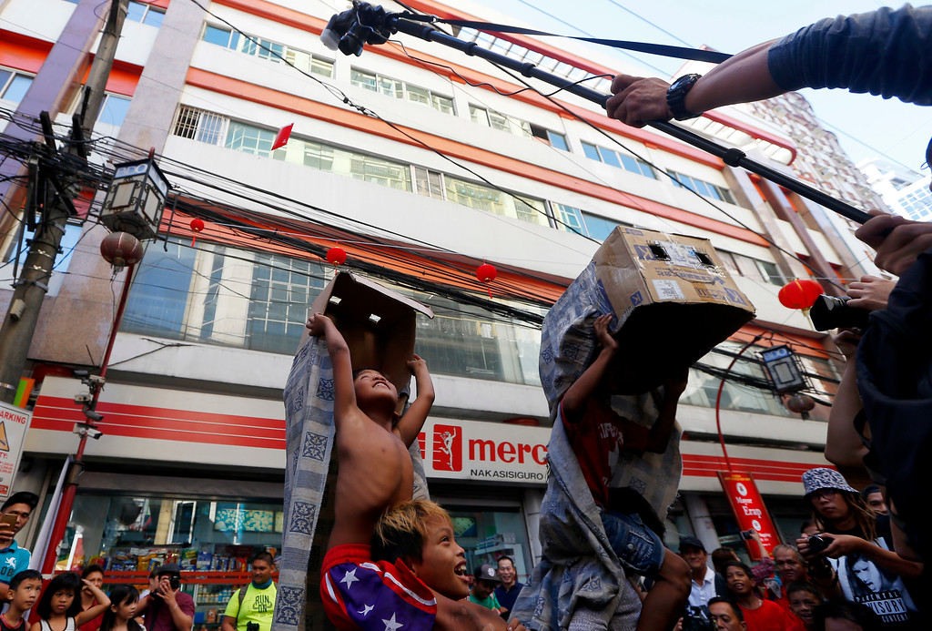 """. A photographer sets up his shots by dangling an envelope containing cash known as \""""Angpao\"""" to enterprising Filipino children, who use improvised lion costumes, while performing a lion dance in celebration of the Chinese Lunar New Year Friday, Feb. 16, 2018 at Manila\'s Chinatown district in Manila, Philippines. This year is the Year of the Earth Dog in the Chinese Lunar calendar. (AP Photo/Bullit Marquez)"""