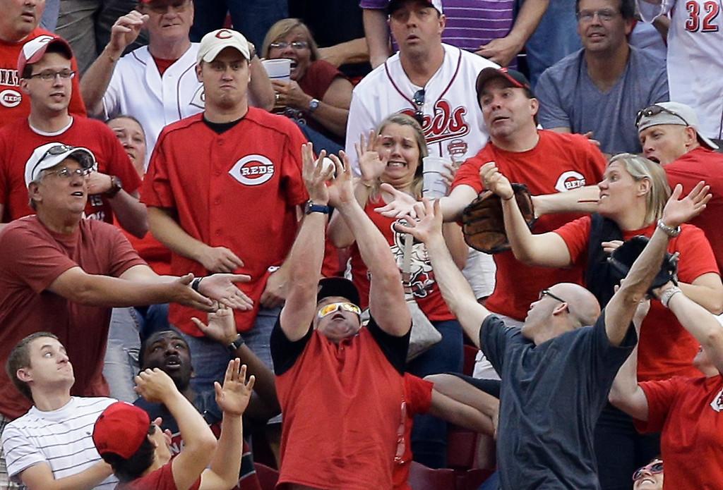 . A fan catches a three-run home run hit by Cincinnati Reds\' Xavier Paul off Colorado Rockies\' Jon Garland in the first inning of a baseball game, Wednesday, June 5, 2013, in Cincinnati. (AP Photo/Al Behrman)