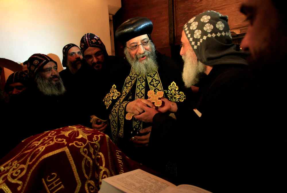 Description of . A clergyman greets Egypt\'s Coptic Christian pope, Tawadros II, center, during an early morning mass at the historic al-Muharraq Monastery, a centuries-old site some 180 miles (300 kilometers) south of Cairo in the province of Assiut. Egypt,Monday, Feb. 5, 2013. Egypt\'s Coptic Christian pope sharply criticized the country\'s Islamist leadership in an interview with The Associated Press on Tuesday, saying the new constitution is discriminatory and Christians should not be treated as a minority. (AP Photo/Khalil Hamra)