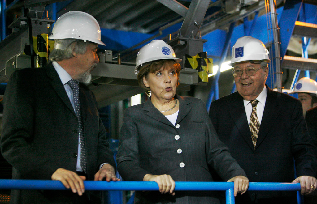 . In this Tuesday, April 29, 2008 file photo made by Associated Press photographer Anja Niedringhaus,  German chancellor Angela Merkel, center, grimaces, as she tours CERN, the European Organization for Nuclear Research, with Rolf Heuer, CERN Director designated, left, and Robert Aymar, Director General CERN, in Geneva, Switzerland.  (AP Photo/Anja Niedringhaus, File)