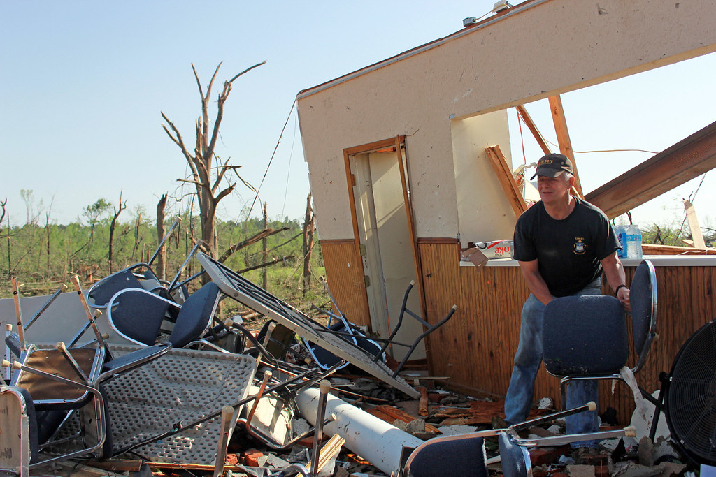 . Mike Pettigrew moves chairs in the badly damaged building that once was the American Legion in Tupelo, Miss Tuesday, April 29, 2014.  (AP Photo/Zachary Odom)