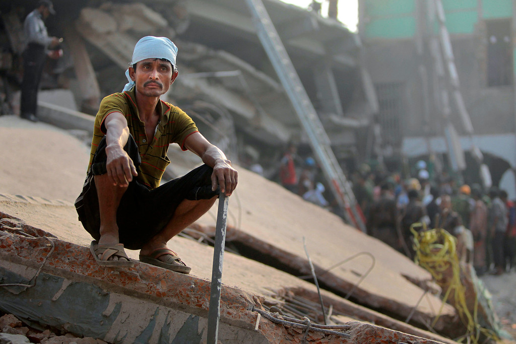 . A Bangladeshi rescue worker takes a break at the site of a building that collapsed Wednesday in Savar, near Dhaka, Bangladesh,Thursday, April 25, 2013.   (AP Photo/A.M.Ahad)