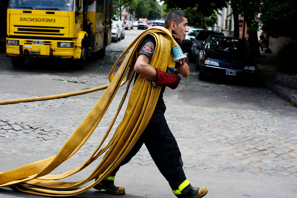 . A firefighter carries a fire hose outside the Iron Mountain warehouse in Buenos Aires, Argentina, Wednesday, Feb. 5, 2014.  (AP Photo/Rodrigo Abd)