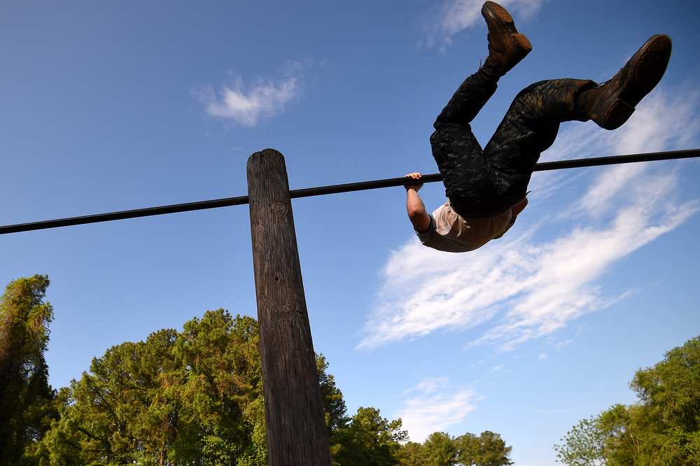 . A member of the United States Naval Academy freshman class flips over a bar on a obstacle course during the annual Sea Trials training exercise at the U.S. Naval Academy on May 13, 2014 in Annapolis, Maryland. (Photo by Patrick Smith/Getty Images)