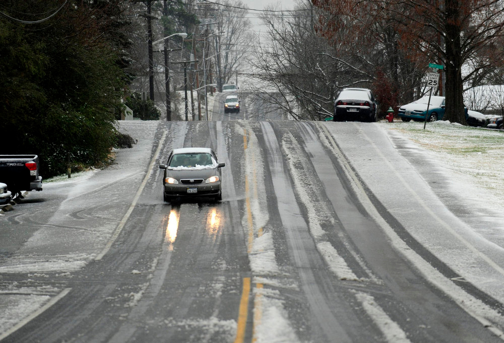 . Cars navigate a slushy S. East Street near Yowell Meadow park in the town of Culpeper, Va. An overnight storm brought rain, snow and ice to the Culpeper area on Wednesday, Dec. 26 2012. (AP Photo/The Free Lance-Star, Reza A. Marvashti)