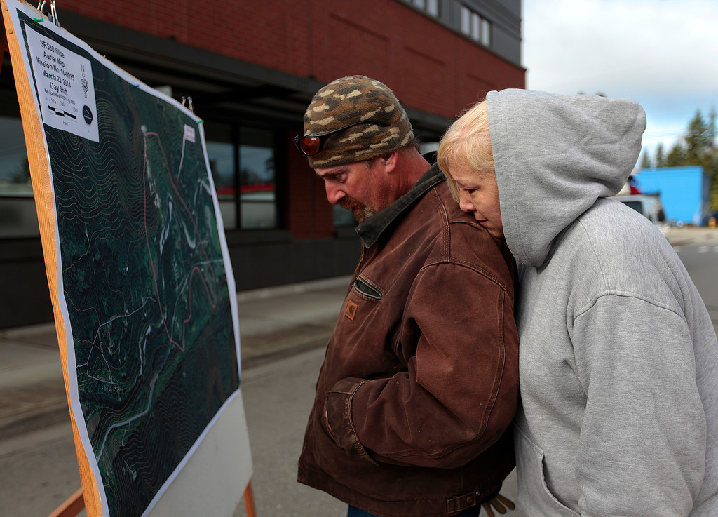 . Paul and Keenan Kimball pause to look at the map of the mudslide area outside of the Arlington City Hall Sunday, March 23, 2014. The Kimball\'s house is just feet from the Stillaguamish River near the mudslide area.  (AP Photo /The Herald, Mark Mulligan)