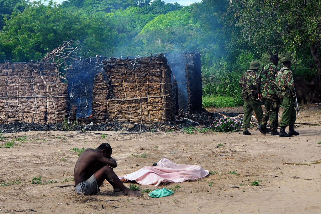 . Security officers walk away as a man mourns next to the bodies of his wife and daughter, who were gunned down outside their house as they attempted to escape when suspected Orma raiders attacked their village of Kibusu in Kenya Thursday, Jan. 10, 2013. The raiders set more than twenty houses on fire and killed at least ten people as the Tana River County ethnic clashes erupted yet again. (AP Photo)