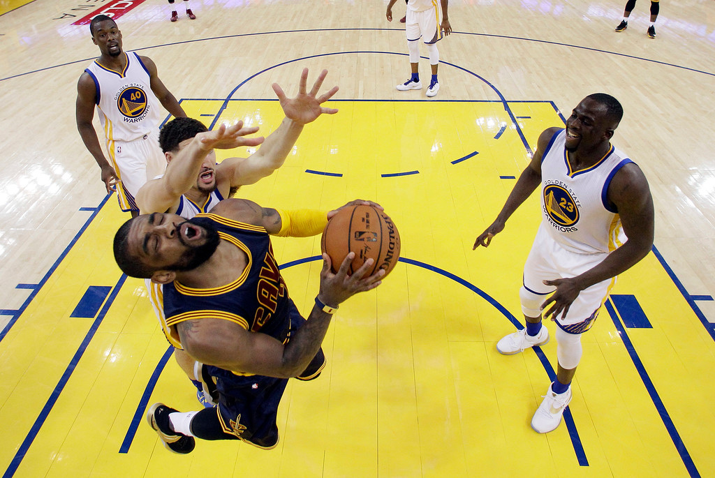 . Cleveland Cavaliers\' Kyrie Irving, bottom left, tries to get a shot past Golden State Warriors\' Klay Thompson, left, and Draymond Green (23) during the first half in Game 1 of basketball\'s NBA Finals Thursday, June 2, 2016, in Oakland, Calif. (AP Photo/Marcio Jose Sanchez, Pool)