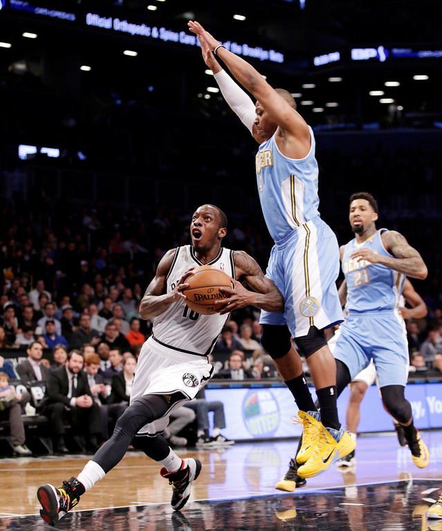 . Denver Nuggets guard Randy Foye (4) defends as Brooklyn Nets guard Tyshawn Taylor looks for his shot in the first half of an NBA basketball game Tuesday, Dec. 3, 2013, in New York. (AP Photo/Kathy Willens)