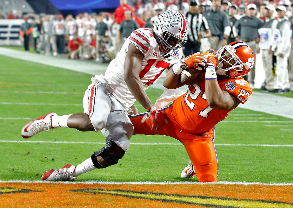 . Clemson running back C.J. Fuller (27) makes a touchdown catch as Ohio State cornerback C.J. Saunders (17) defends during the first half of the Fiesta Bowl NCAA college football game, Saturday, Dec. 31, 2016, in Glendale, Ariz. (AP Photo/Ross D. Franklin)