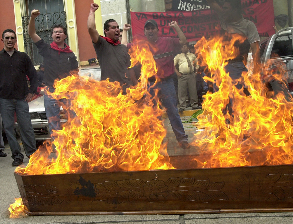 . Protesters burn a coffin that symbolizes the death of Guatemala\'s Constitutional Court in front of the Electoral Supreme Tribunal in Guatemala City, on Wednesday, July 16, 2003. More than 30 social organizations condemned the country\'s highest court for clearing the way for former dictator Efrain Rios Montt to run for president in the November 2003 elections.(Ap photo/ Rodrigo Abd)