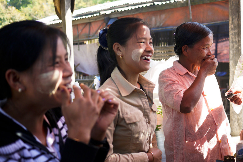 The betel nut vendors laugh heartily as one of the men in our group tries the betel nut leaves concoction on Inle Lake, Burma (Myanmar).