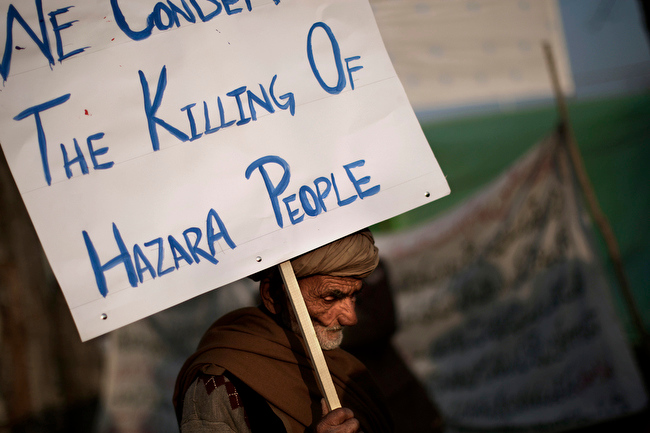 Description of . An elderly Pakistani man holds a banner while taking part in a protest condemning the bombing attack that took place in Quetta last Saturday, in Islamabad, Pakistan, Monday, Feb. 18, 2013. The families of scores of victims of the bombing in Quetta have refused to bury their relatives until authorities take action against the militants who were responsible. (AP Photo/Muhammed Muheisen)