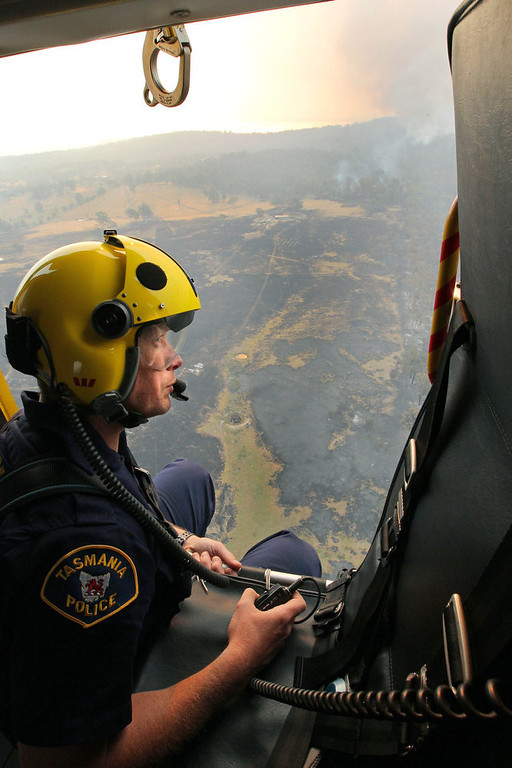. Westpac Police rescue helicopter crewman Sgt. Matthew Drumm surveys the fire near Dunalley, east of the Tasmanian capital of Hobart, Australia, on Saturday, Jan. 5, 2013.   Australian officials battled a series of wildfires amid scorching temperatures across the country on Saturday, with one blaze destroying dozens of homes in the island state of Tasmania. (AP Photo/Chris Kidd, Pool)