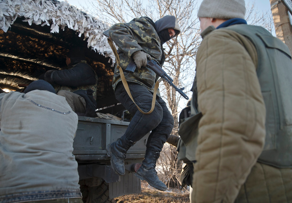 . An Ukrainian serviceman jumps off a broken down vehicle outside Artemivsk, Ukraine, while pulling out of Debaltseve, Wednesday, Feb. 18, 2015. After weeks of relentless fighting, the embattled Ukrainian rail hub of Debaltseve fell Wednesday to Russia-backed separatists, who hoisted a flag in triumph over the town. The Ukrainian president confirmed that he had ordered troops to pull out and the rebels reported taking hundreds of soldiers captive.(AP Photo/Vadim Ghirda)