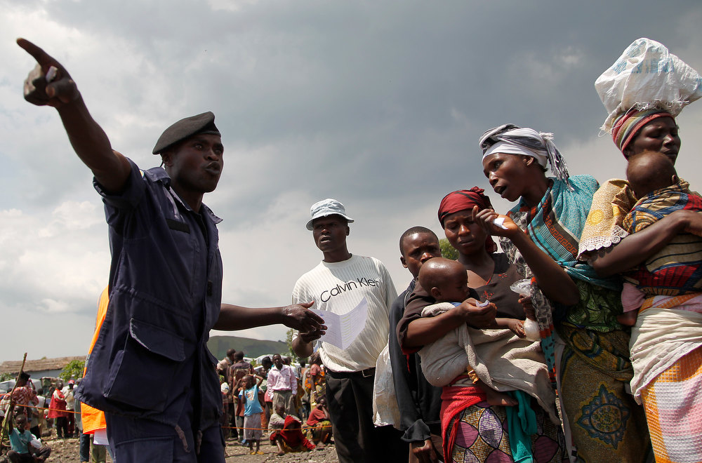 . A Congolese national police officer directs internally displaced Congolese women waiting for food to be distributed by WFP at the Mugunga 3 camp outside the eastern Congolese town of Goma Sunday Dec. 2, 2012. Rebels say they will take back Congo\'s city of Goma if the government does not agree to negotiate with them by Monday. The M23 rebels completed their withdrawal of the eastern Congo city on Saturday, in compliance with an agreement reached between the rebel group and a regional body. (AP Photo/Jerome Delay)