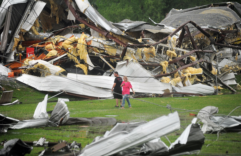 . A man and woman examine the twisted wreckage of Glass Masters on U.S. 49 Frontage Road in Richland,  Miss., shortly after it was destroyed by a tornado late Monday afternoon, April 28, 2014.   With parts of the U.S. recovering from deadly tornadoes, more heavy storms are making their way across the South.  (AP Photo/The Clarion-Ledger, )