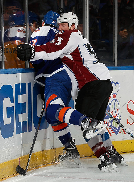 . UNIONDALE, NY - FEBRUARY 08:  Cody McLeod #55 of the Colorado Avalanche checks Brian Strait #37 of the New York Islanders during the first period of an NHL hockey game at Nassau Veterans Memorial Coliseum on February 8, 2014 in Uniondale, New York.  (Photo by Paul Bereswill/Getty Images)