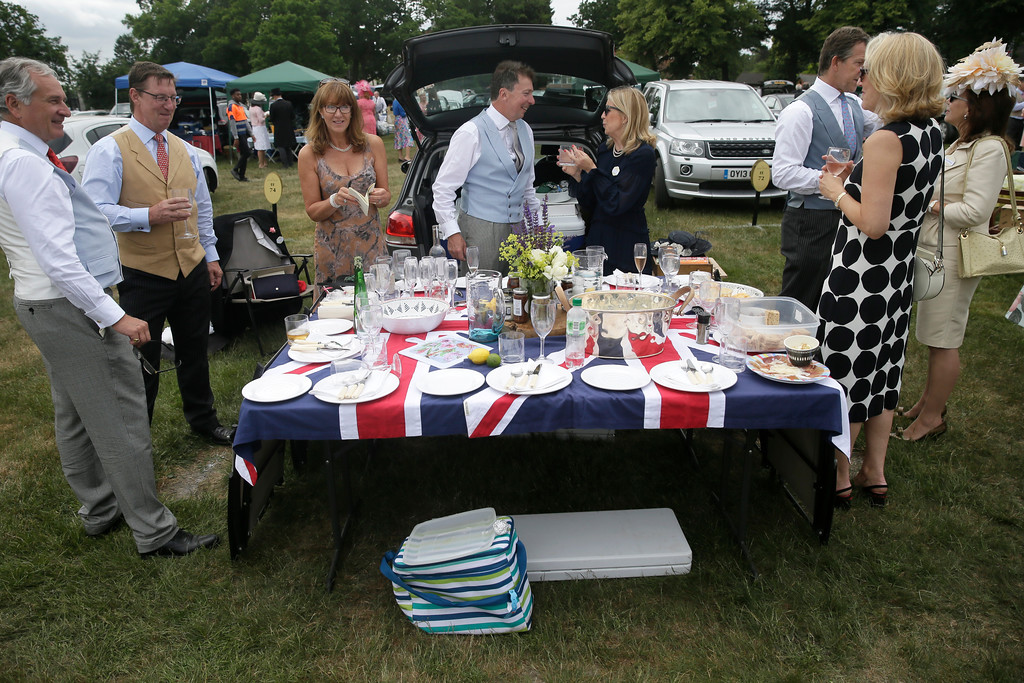 . Racegoers drink and eat on the second day of the Royal Ascot horse race meeting in Ascot, England, Wednesday, June 20, 2018. (AP Photo/Tim Ireland)