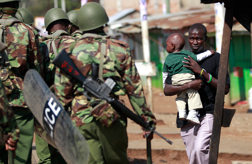 . A man carrying a child walks towards riot police as tension arises after Uhuru Kenyatta was declared winner of Kenya\'s presidential election, in Nyallenda slums in Kenya\'s western town of Kisumu, 350km (218 miles) from the capital Nairobi, March 9, 2013.  REUTERS/Thomas Mukoya