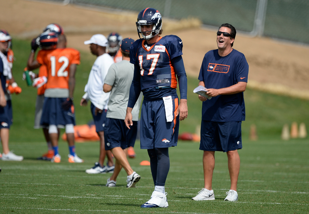 . Denver Broncos quarterbacks coach Greg Knapp laughs out during drills as Denver Broncos quarterback Brock Osweiler (17) prepares for the snap during practice August 26, 2014 at Dove Valley.(Photo by John Leyba/The Denver Post)