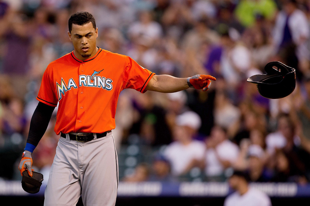. Giancarlo Stanton #27 of the Miami Marlins tosses his helmet after lining out to end the fifth inning against the Colorado Rockies at Coors Field on July 23, 2013 in Denver, Colorado.  (Photo by Justin Edmonds/Getty Images)