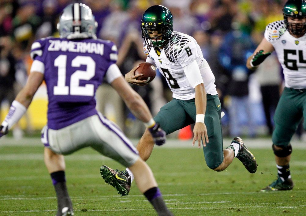 . Oregon quarterback Marcus Mariota (8) tries to avoid Kansas State defensive back Ty Zimmerman (12) during the first half of the Fiesta Bowl NCAA college football game, Thursday, Jan. 3, 2013, in Glendale, Ariz. (AP Photo/Paul Connors)