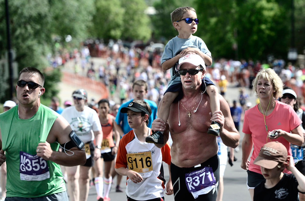 . Greg Ritscher carries his grandson Haven Heimer as they near the finish line on the hill outside Folsom Field during the 2013 Bolder Boulder in Boulder Colorado.  Photo by Paul Aiken / The Boulder Daily Camera / May 27, 2013