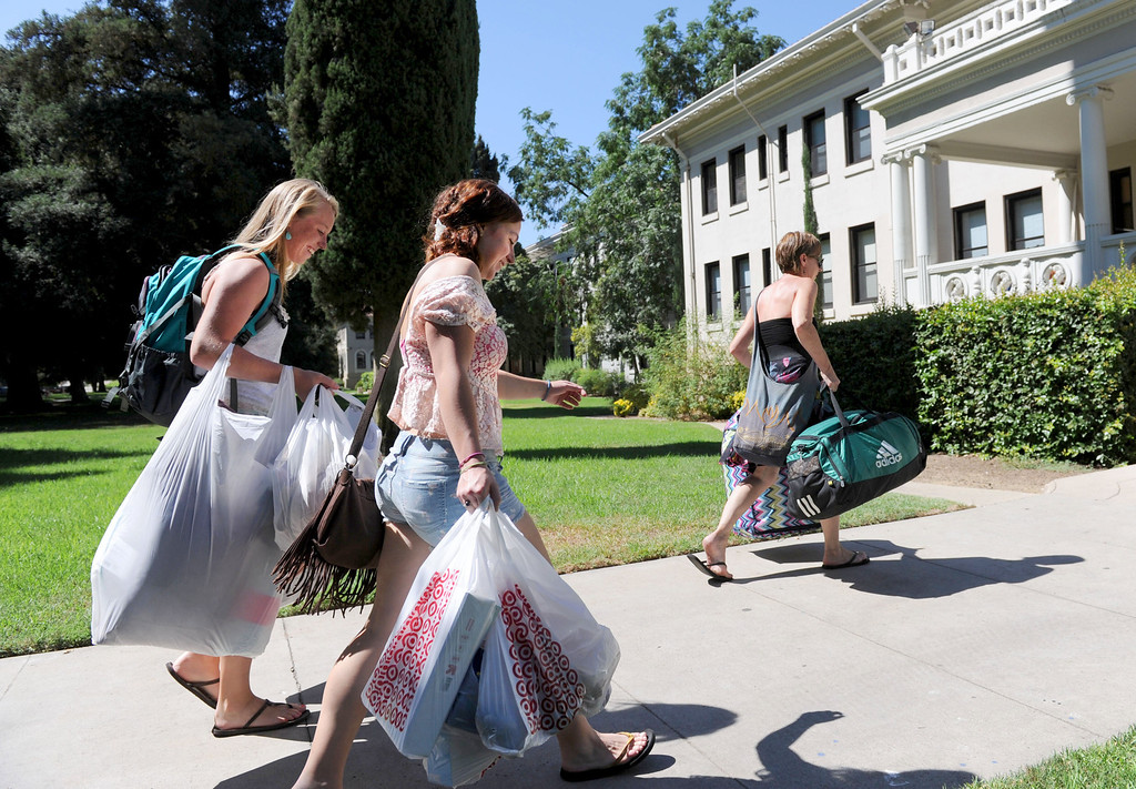 . (John Valenzuela/Staff Photographer) Students Erin Gaffney (left) and Sydney Finkbohner (right) move their belonging into the Fairmont dorm, with helps from Lynn Finkbohner, Wednesday moring during move-in day at the University of Redlands, August 28, 2013.