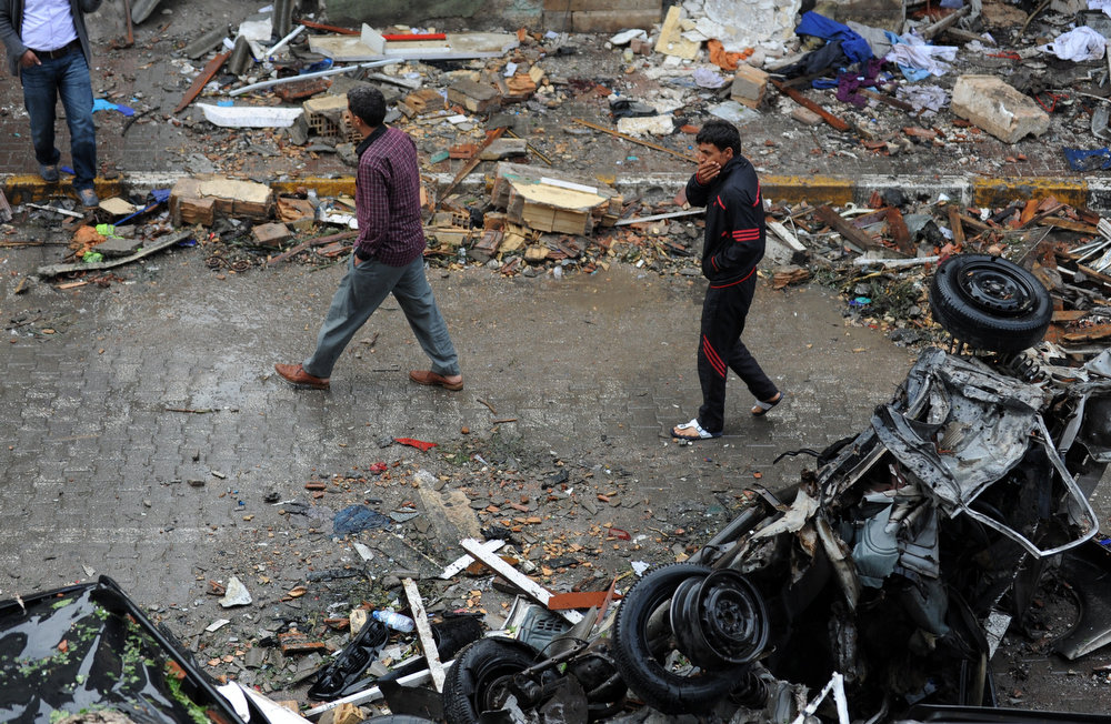 . Men walk in a street strewn with debris on May 12, 2013 after a car bomb explosion went off on May 11 in Reyhanli in Hatay, just a few kilometers from the main border crossing into Syria. Turkey was reeling from twin car bomb attacks which left at least 43 people dead in a town near the Syrian border, with Ankara blaming pro-Damascus groups and vowing to bring the perpetrators to justice. BULENT KILIC/AFP/Getty Images