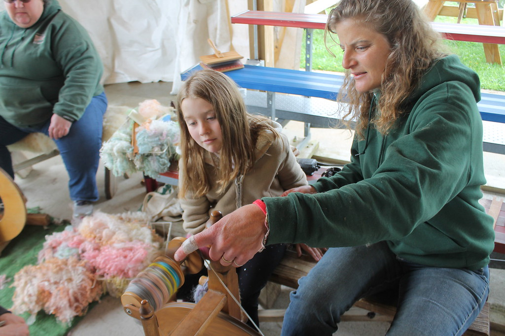 . Alexis Swiatkowski, 7, Fairview Park works with Farmpark interpreter Wendy Vacik to spin wool into yard during the Farmpark\'s sheep shearing weekend on May 13. Kristi Garabrandt - The News-Herald