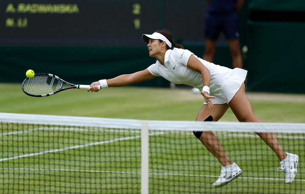 . Li Na of China stretches to play a return to Agnieszka Radwanska of Poland in their Women\'s singles quarterfinal match at the All England Lawn Tennis Championships in Wimbledon, London, Tuesday, July 2, 2013. (AP Photo/Sang Tan)